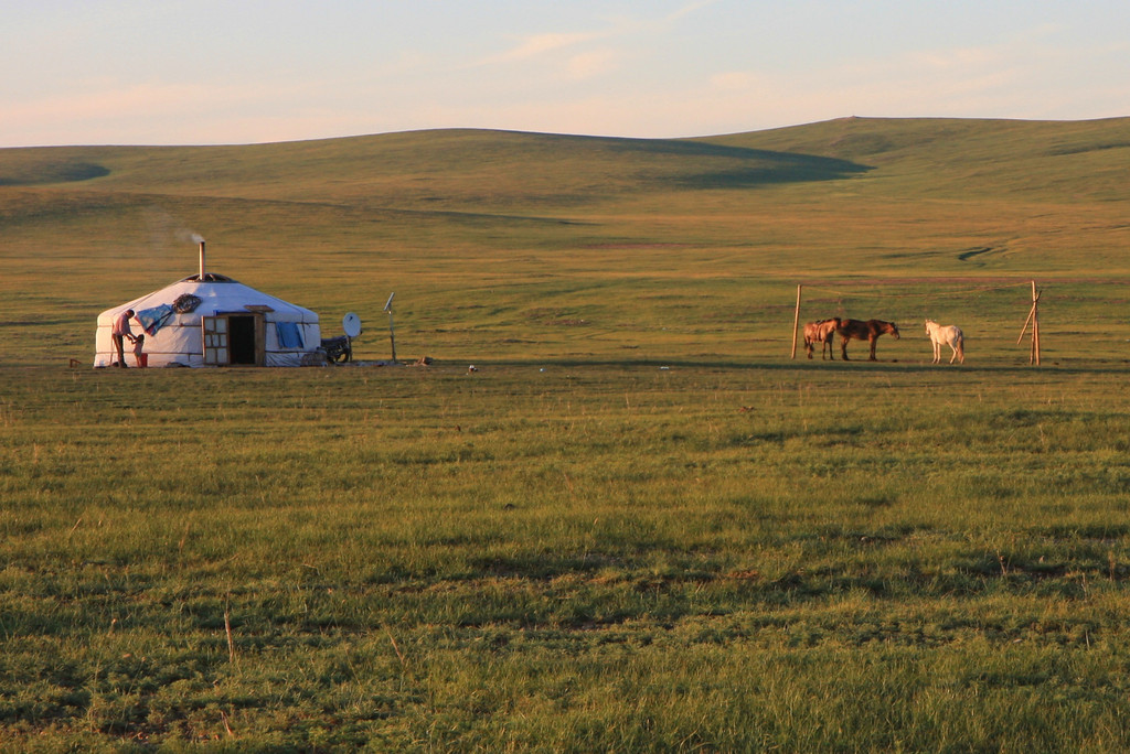 A family doing chores around their ger before sunset near Ulaanbaatar
