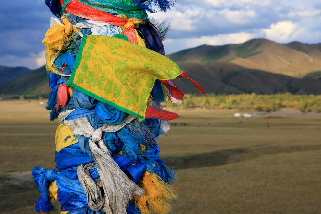 An ovoo (religious site) covered in 'offerings' of color