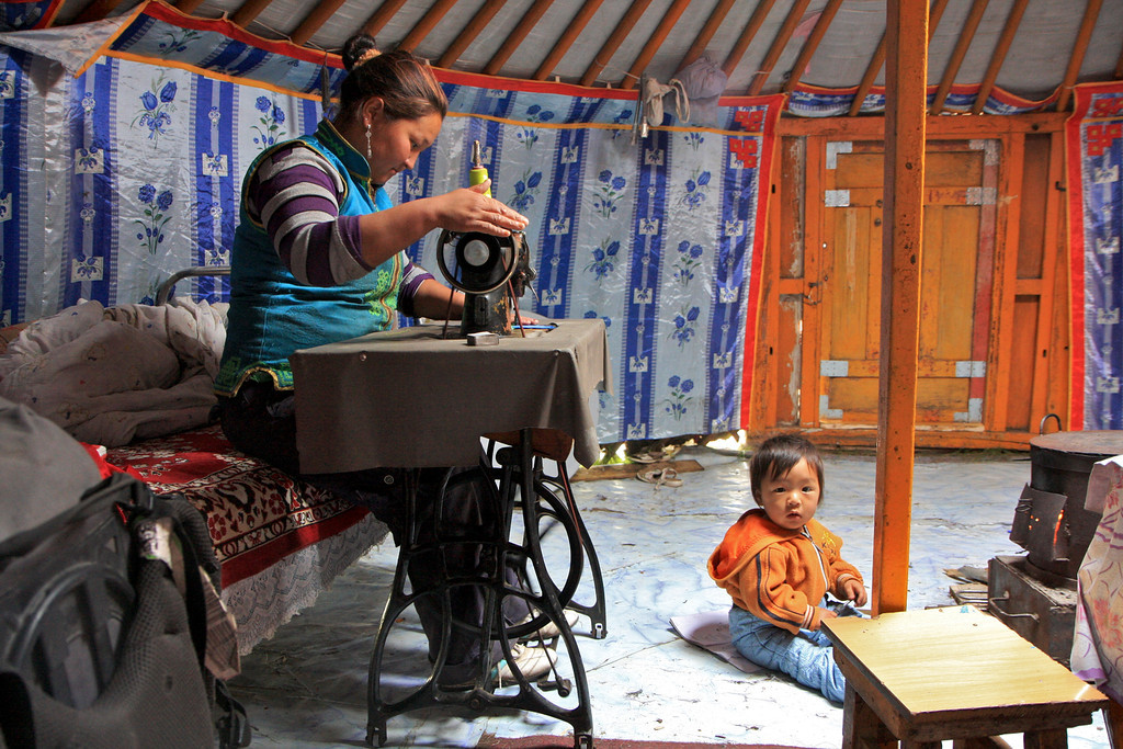 A mother sews Mongolian trinkets inside her ger