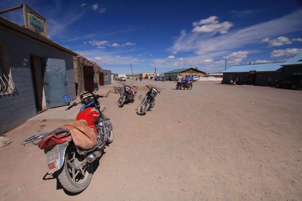 Motorcycles parked in a typical village 'main street' in Western Mongolia